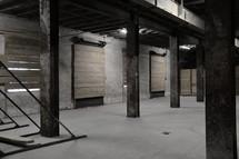 An empty storage space in a commercial building.  room, storage room, storage, storeroom, storage space, space, empty, store room, whitewashed, wall, walls, industrial, building, white, dirty, dirt, grime, industry, manufacture, hall, mural, stone, stones, strut, struts, pillar, pillars, buttress, column, columns, upright, stilt, T-girder, double T-girder, I-beam, metal, ferric, iron, gate, gates, fluorescent light, neon light, hangar