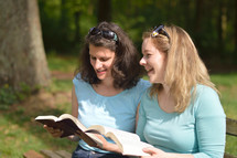 Young women smiling while reading in the bible together sitting outside on a bench on a sunny day. 