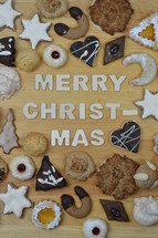 different kinds of Christmas cookies on a breadboard around the words: MERRY CHRISTMAS