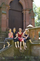 friends sitting together in front of a church