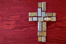 many little presents shaping a cross on red wooden background