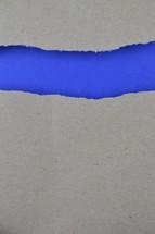 torn gray paper exposing blue