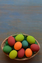Easter eggs in a basket on blue wood background
