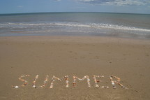 word summer written in the sand with seashells