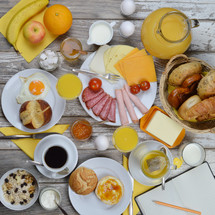 breakfast table with lots of fresh food like coffee, rolls, cheese, eggs, orange juice, tea, jam, butter, banana, apple, orange and a basket full of croissant, rolls and pretzel