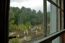 View of Grave markers in a small rural cemetery through a window.