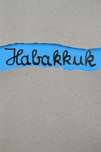 torn open kraft paper over blue paper with the name of the prophetic book Habakkuk