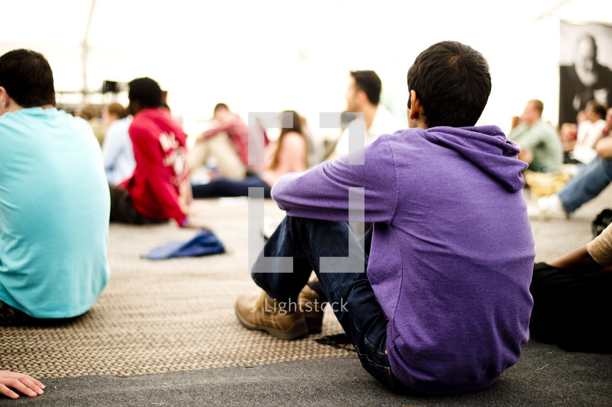 Teens sitting on the floor during a worship study.