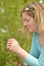 Young blond woman praying outdoors. 