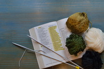 wool and knitting needles on a bible open at the page of Proverbs 31 with the passage marked: The Wife of Noble Character  Vers 10 to 31