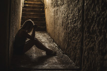 a woman sitting alone in a dark hallway