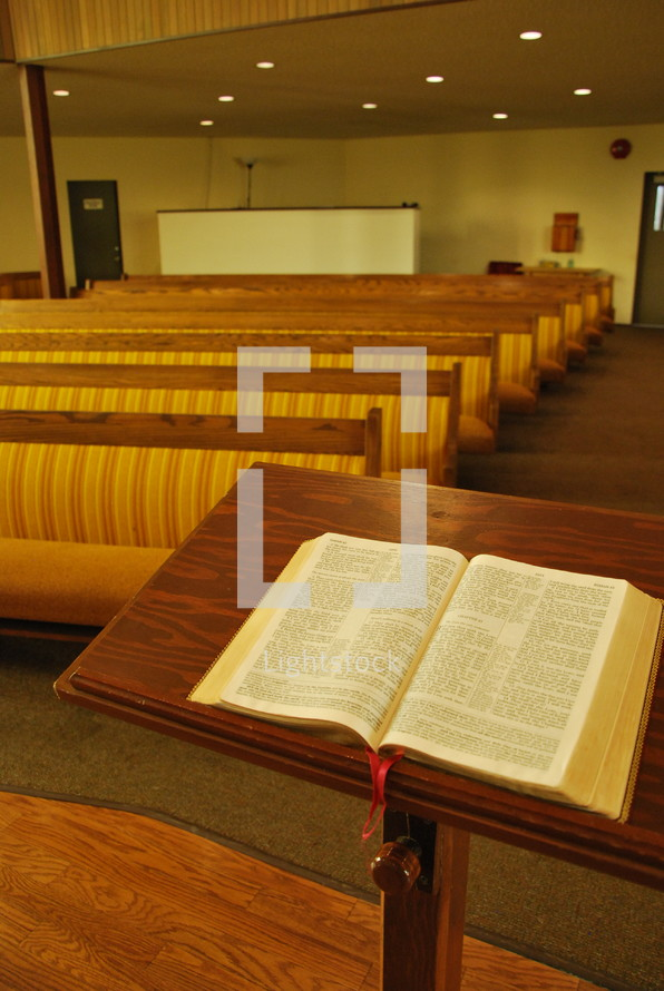 Bible at the pulpit and rows of church pews
