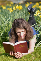 Woman reading the bible while laying in a meadow between daffodils.