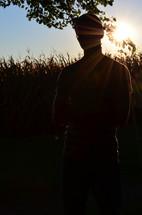 a young man standing beside a corn field