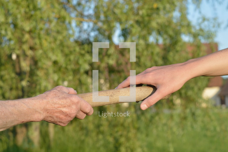 old woman giving the relay baton to the next generation into her daughter's hand
