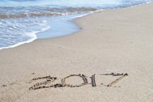 tide washing onto a beach with the year 2017 in the sand