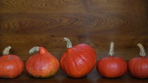 row of five orange red Hokkaido pumpkins on wooden ground