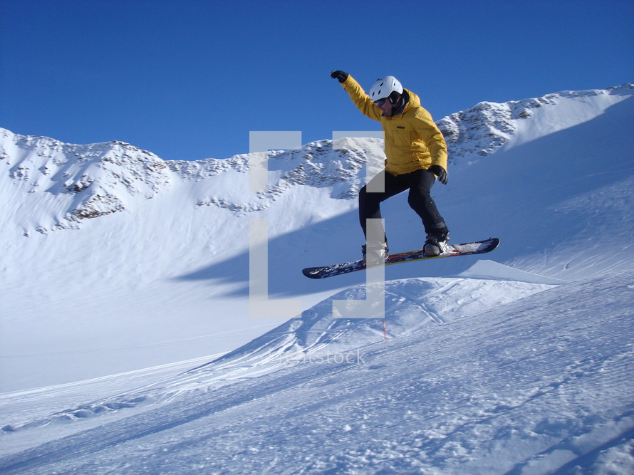 A man taking a jump on his snowboard.