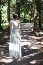 a woman in a long dress standing on a path in a forest