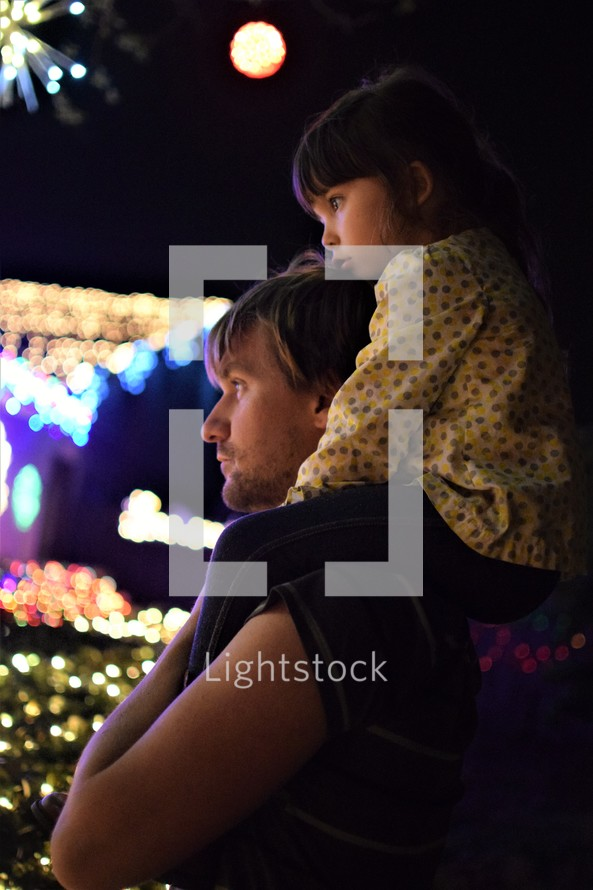a little girl on her father's shoulders