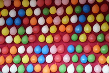 colorful balloons pinned at a pink wall at a fair