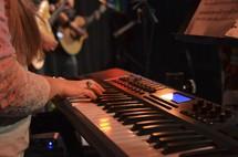 A woman playing a keyboard.