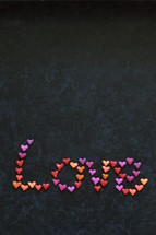 the word LOVE written with many little colorful clay hearts on black background