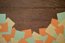 border of blank orange, yellow and green notepads on wooden planks