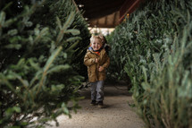 a toddler boy walking through a Christmas tree lot
