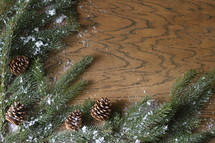 pine cones, snow, and pine boughs on a wooden  background