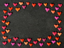 colorful clay hearts frame on a black slate background