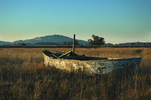Weathered sailboat in a grassy field.