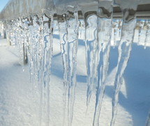 Icicles dripping toward to snowy ground.