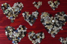 many little buttons shaping hearts on a red wooden background