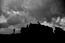 Silhouettes of people on a rock shelf.