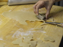 Woman pricking heart shaped marzipan pieces out of the marzipan dough for Christmas cookies