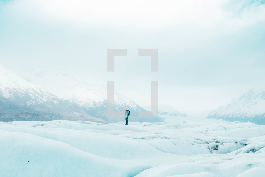 a man hiking a snow covered mountain landscape