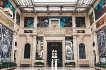 man and woman walking through an art museum