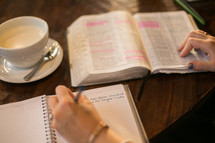 a woman reading a Bible and writing in a journal sitting at a table in a coffee shop