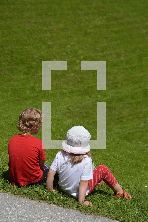 two little children sitting in the grass and watching something far away.
