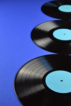 three old black vinyl records with blank cyan labels on blue background