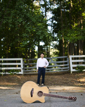 a guitar in front of a man standing near a fence outdoors