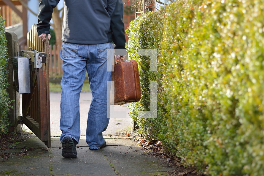 man leaving home with a suitcase for a journey