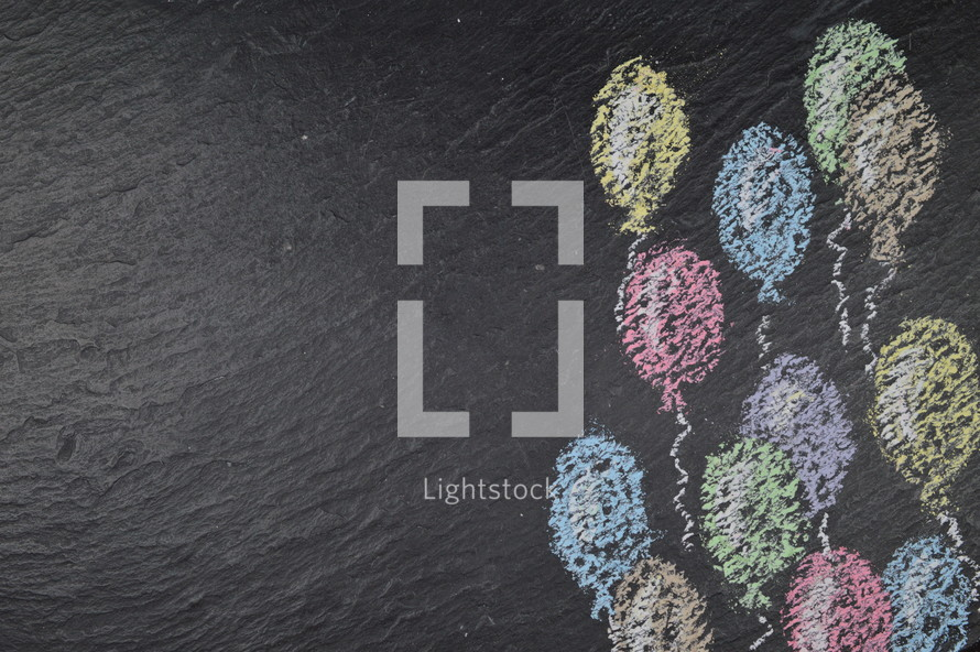 chalk on slate with flying balloons and copy space to the left side