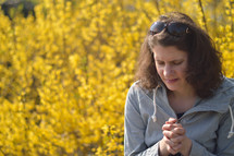 Young brunette woman praying with closed eyes while sitting outdoors in front of a bright yellow blooming forsythia bush.