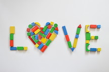 colorful wooden toy blocks shaping the form of a heart as an O in the word LOVE