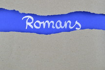 word Romans exposed under gray torn paper