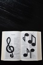 A Bible open to Psalms covered in musical notes.