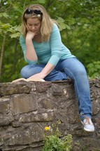 a woman sitting on a stone wall reading a Bible