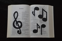 Bible open to Psalms covered in musical notes.